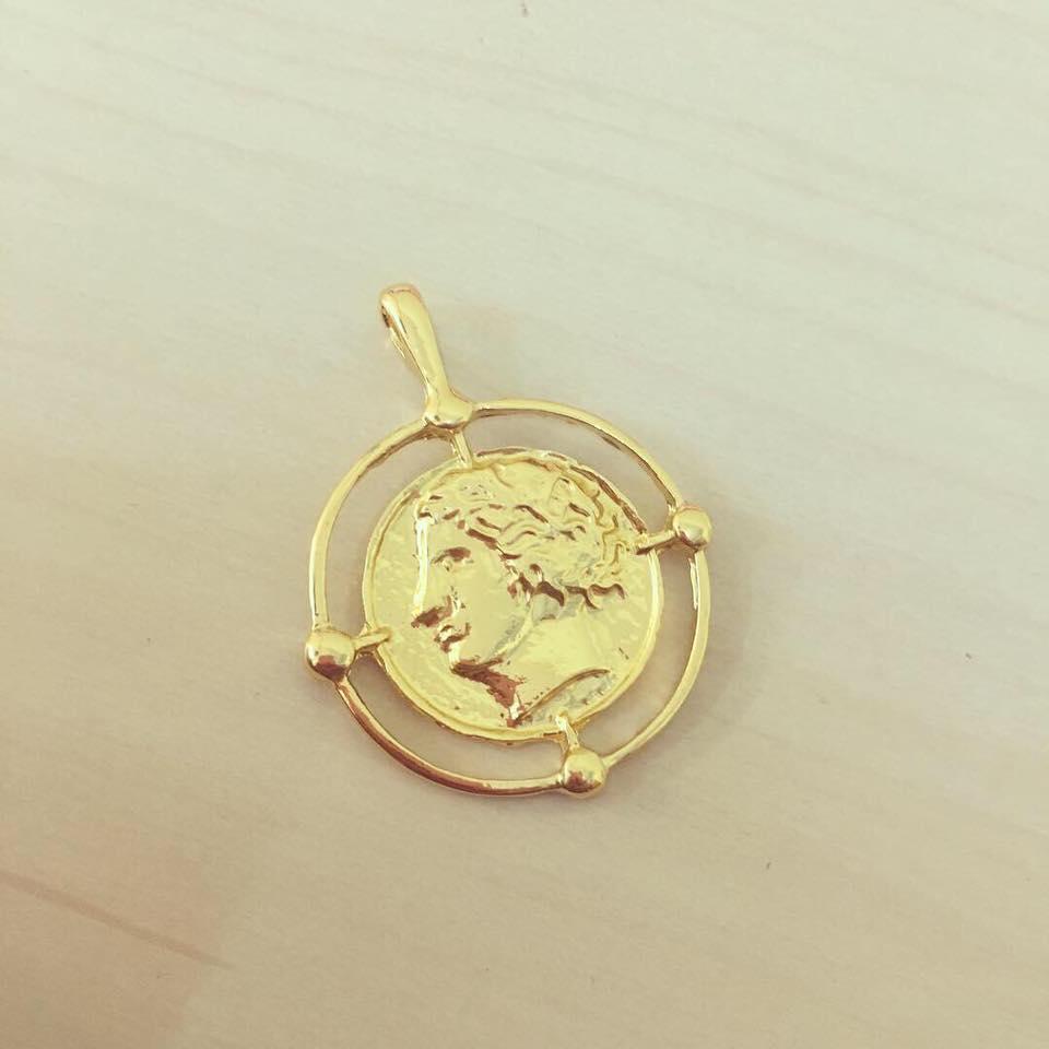 Moeda Dourada em Armação Circular